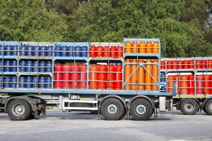 Trucks parked on a street load of colored propane gas tanks