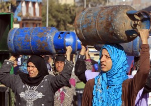 Women carry gas cylinders to be refilled at a distribution point in Cairo January 19, 2015. Egypt is going through its worst energy crisis in decades and is seeking fresh sources of natural gas, which powers most of its homes and factories.   REUTERS/Mohamed Abd El Ghany (EGYPT - Tags: ENERGY SOCIETY BUSINESS COMMODITIES POLITICS) - RTR4M0SS